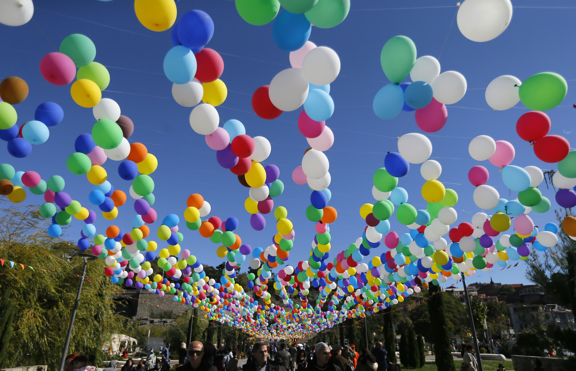 epa05586454 Georgian people walk under balloons as they attend the 'Tbilisoba' celebrations in Tbilisi, Georgia, 15 October 2016. The annual festival is dedicated to the Georgian capital of Tbilisi.  EPA/ZURAB KURTSIKIDZE