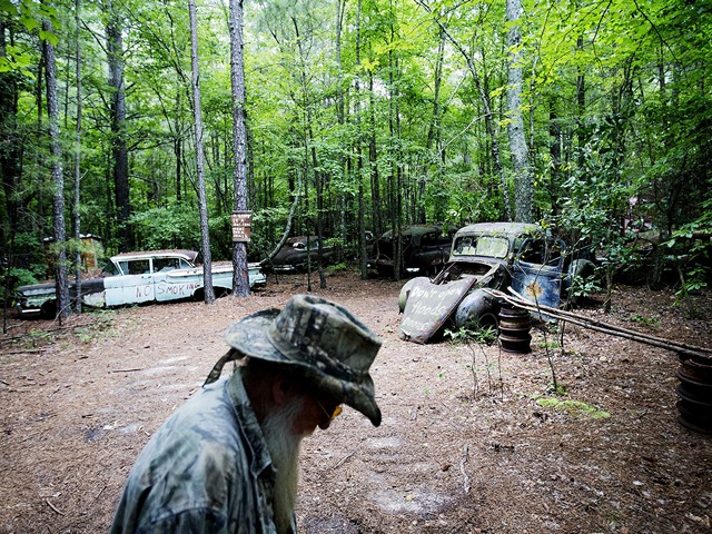 Eddie McDaniel, who goes by Fast Eddie, walks through Old Car City, the world's largest known classic car junkyard, where he occasionally plays piano for visitors Thursday, July 16, 2015, in White, Ga. Over 4,000 classic cars decorate 32 acres of forest which have been turned into a junkyard museum by owner Walter Dean Lewis. The two grew up playing in the cars on the lot which started as a general store selling auto parts in 1931 by Lewis' parents. Lewis stopped selling parts about six years ago when he realized he could sustain the business more as a museum, charging $15 for visitors just looking, and $25 for photographers. Many of the cars have never moved in over 30 years and in some cases, trees now grow through them, even lifting some off the ground. (AP Photo/David Goldman)